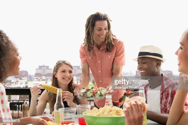 Man serving friends at barbecue outdoors