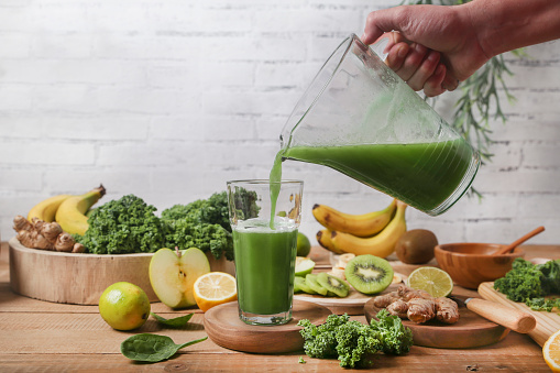 Man serving glass of green smoothie surrounded by ingredients - gettyimageskorea