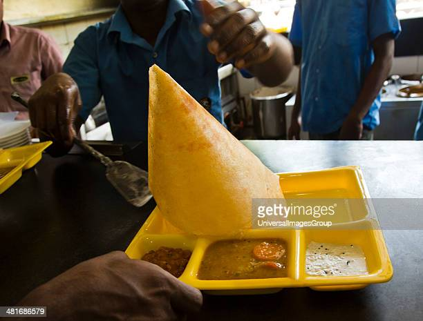 Man serving masala dosa in a restaurant Chennai Tamil Nadu India