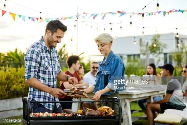 アサドのグリルで肉を仕える男 - バーベキューグリル ストックフォトと画像