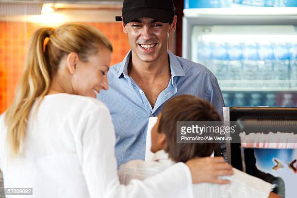 Man serving mother and son at snack counter