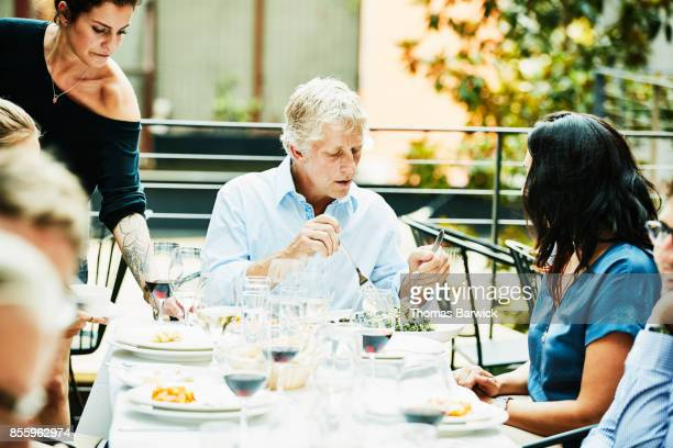 Man serving pasta during celebration dinner with friends on restaurant patio