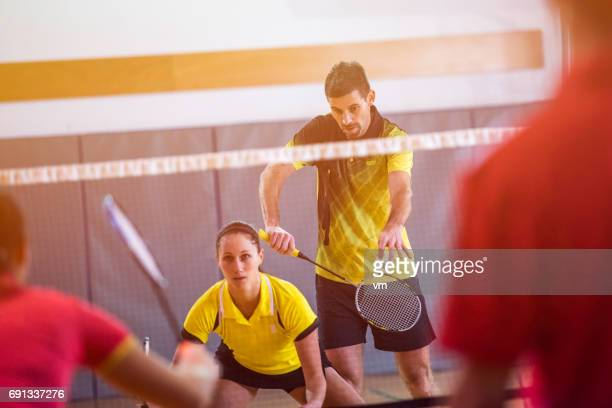 man serving shuttlecock - badminton stock photos and pictures