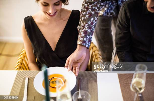 man serving squash soup to woman during dinner party - vネック ストックフォトと画像