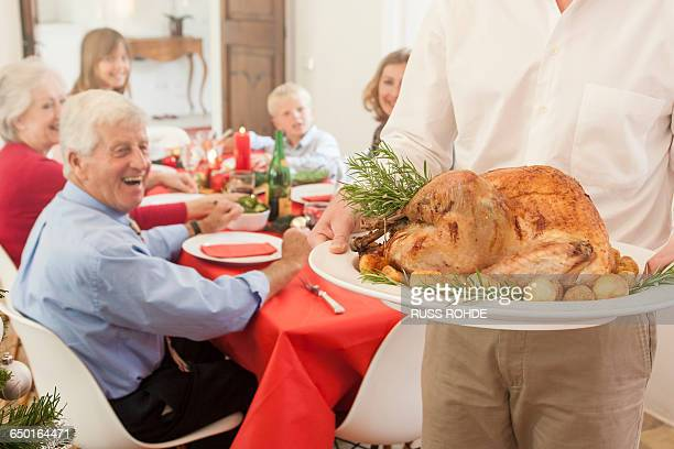 Man serving turkey to family at christmas dinner