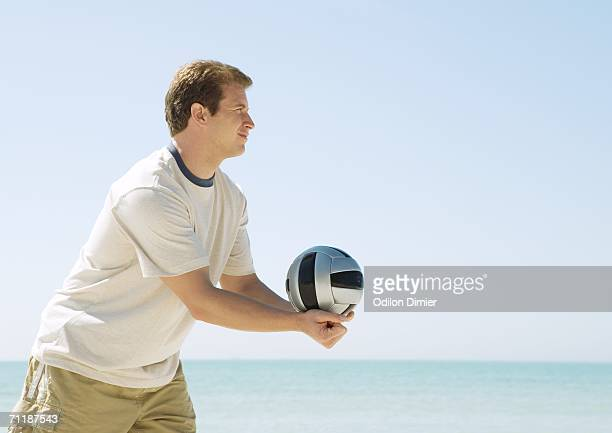man serving volleyball on beach - strand volleyball der männer stock-fotos und bilder