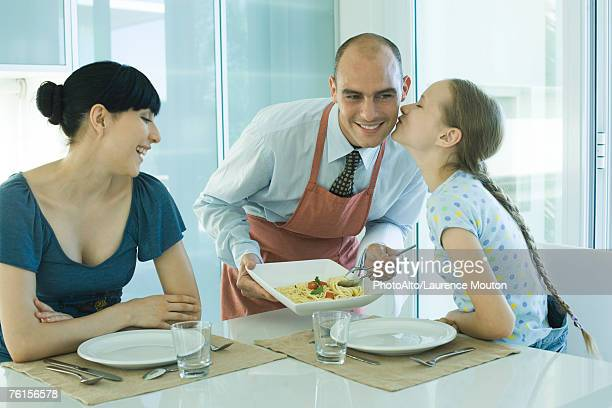 'Man serving wife and daughter spaghetti, girl kissing father on cheek'