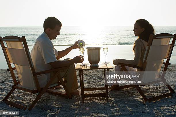 Man serving woman champagne on beach, backlit