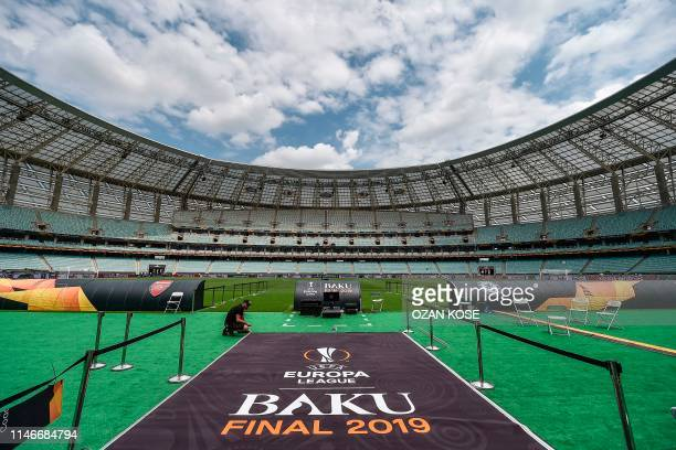 A man sets a carpet at the Baku Olympic stadium on May 28 2019 on the eve of the UEFA Europa league final football match between Arsenal and Chelsea...