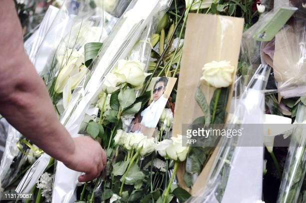 A man sets a flower in front of the house where the five Dupont de Ligonnes family members were murdered and discovered on April 21 on April 26 2011...