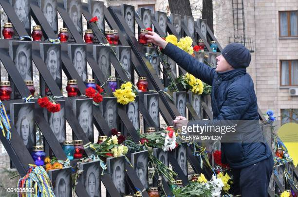 A man sets candle and lays flowers at the memorial for the killed Maidan activists during a ceremony marking the fifth anniversary of the Euromaidan...
