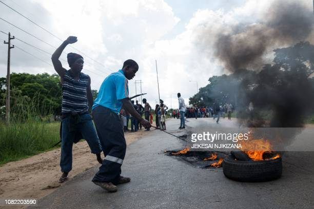 A man sets tyre on fire as angry protesters barricade the main route to Zimbabwe's capital Harare from Epworth township on January 14 2019 after...