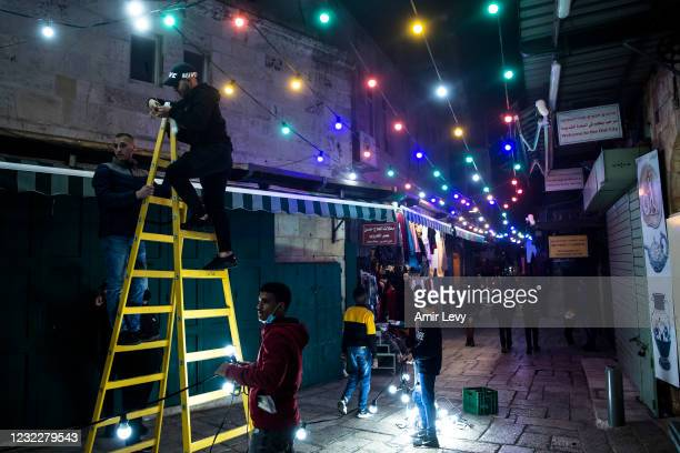 Man sets up a light decoration in Jerusalem's old city on the first evening of the holy Muslim month of Ramadan on April 12, 2021 in Jerusalem,...