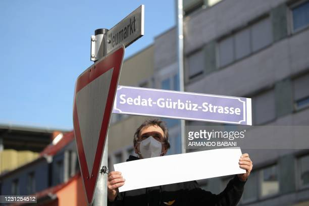 Man sets up a street sign with the name of Sedat Guerbuez, owner of the shisha bar Midnight at the Heumarkt and one of nine victims of the deadly...