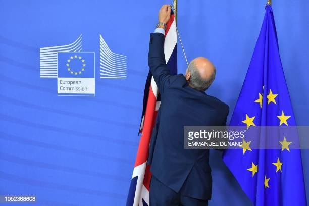 TOPSHOT A man sets up the United Kingdom flag past the EU flag before the arrival of Britain's Prime Minister Theresa May and President of the...