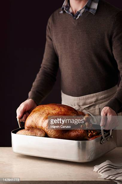 Man setting down cooked turkey in baking dish