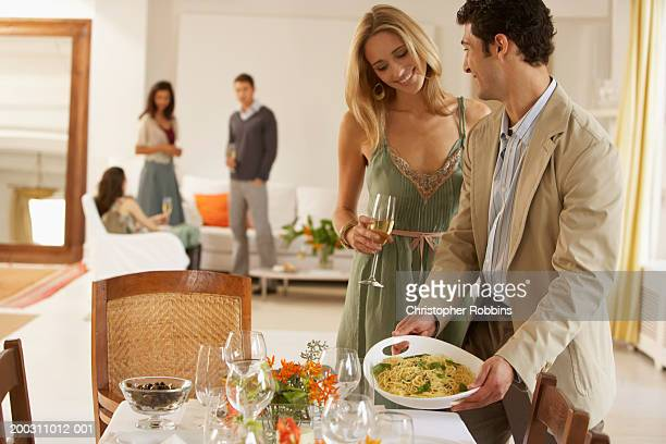 man setting food on dining table, smiling, friends in background - incidental people stock pictures, royalty-free photos & images