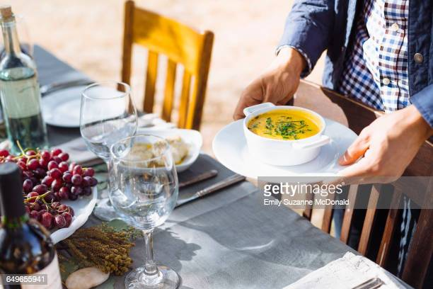 Man setting platter of soup on outdoor table