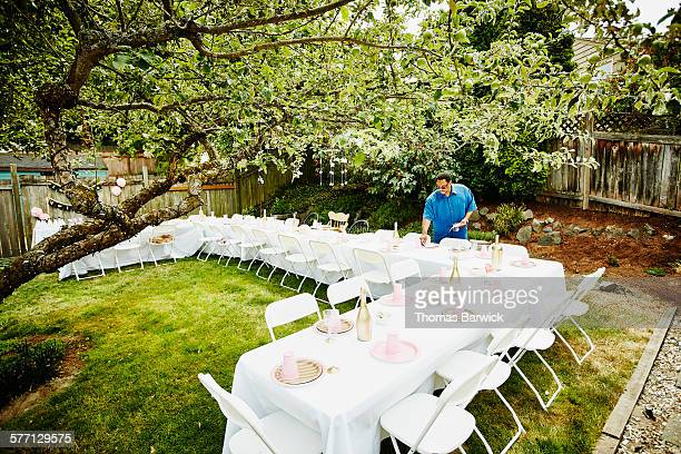 Man setting table for outdoor birthday party