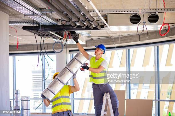 man setting up ventilation system indoors - air duct stock pictures, royalty-free photos & images
