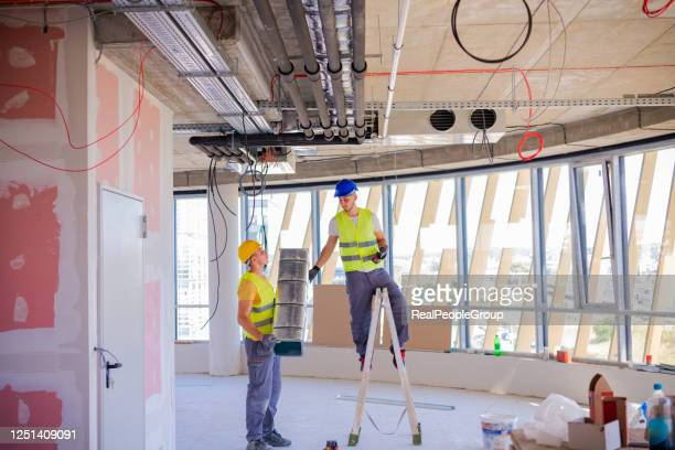 man setting up ventilation system indoors - installation art stock pictures, royalty-free photos & images