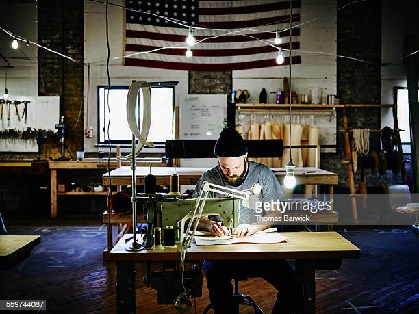 Man sewing canvas bag at industrial sewing machine