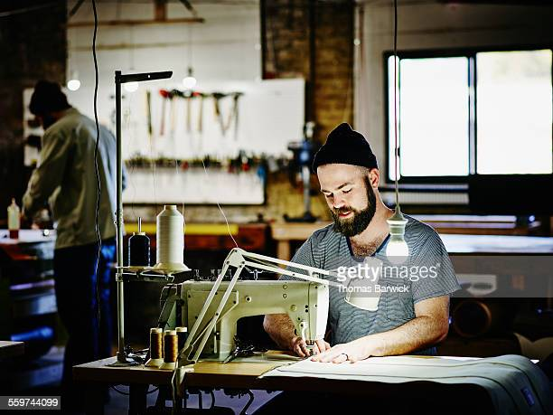 Man sewing canvas bag on industrial sewing machine