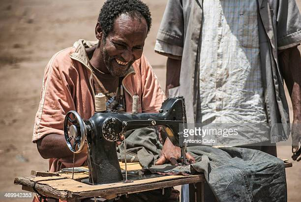 CONTENT] A man sews pants with a sewing machine in the large market of Key Afer one of the most beautiful and picturesque of all the lower Omo Valley...