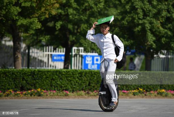 A man shades with a paper bag as he rides a self balance scooter on July 12 2017 in Beijing China The dog days of summer start from July 12 in China