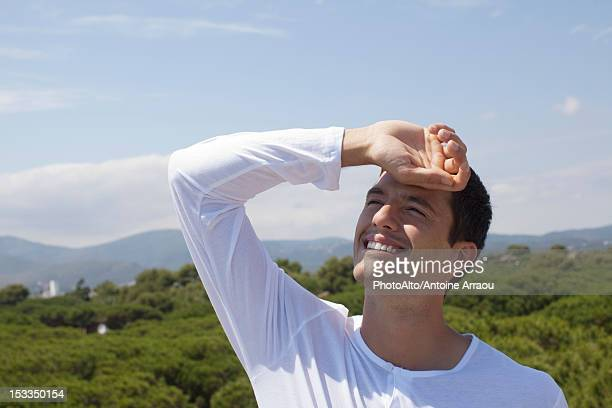 man shading eyes from sun - squinting stock photos and pictures