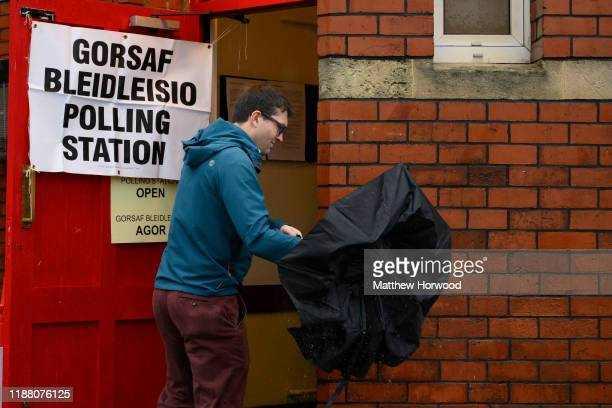 A man shakes an umbrella before entering a polling station on December 12 2019 in Birchgrove Cardiff Wales The current Conservative Prime Minister...