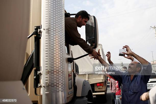 A man shakes hand with an Iraqi Kurdish Peshmerga as Peshmerga forces' military convoy carrying heavy weapons and passing through Nusaybin district...