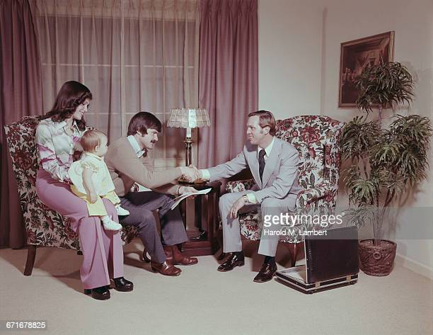 man shaking hand with real estate agent while his wife and daughter sitting besides  - {{relatedsearchurl(carousel.phrase)}} fotografías e imágenes de stock