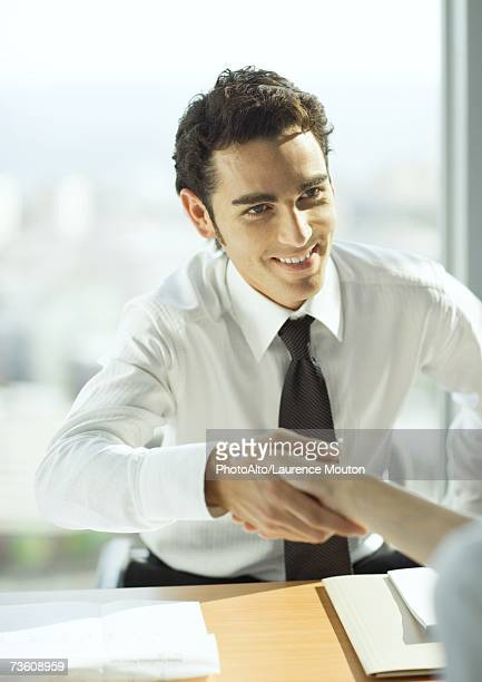 Man shaking hands across table
