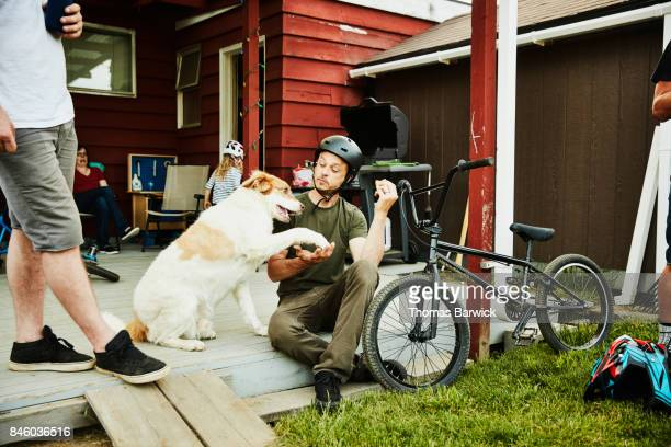 Man shaking hands with dog with eating hot dog on back porch with friends on summer evening