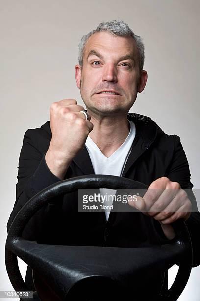 A man shaking his fist behind a car steering wheel