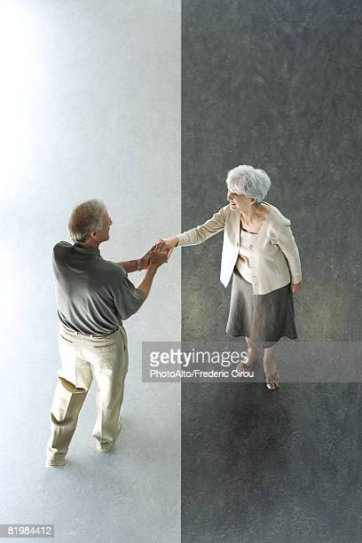 Man shaking woman's hand, high angle view