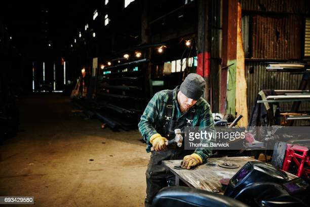 Man shaping metal with hammer for project in metal workshop