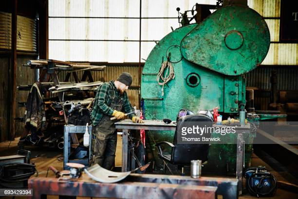 Man shaping piece of metal with hammer for project in metal workshop
