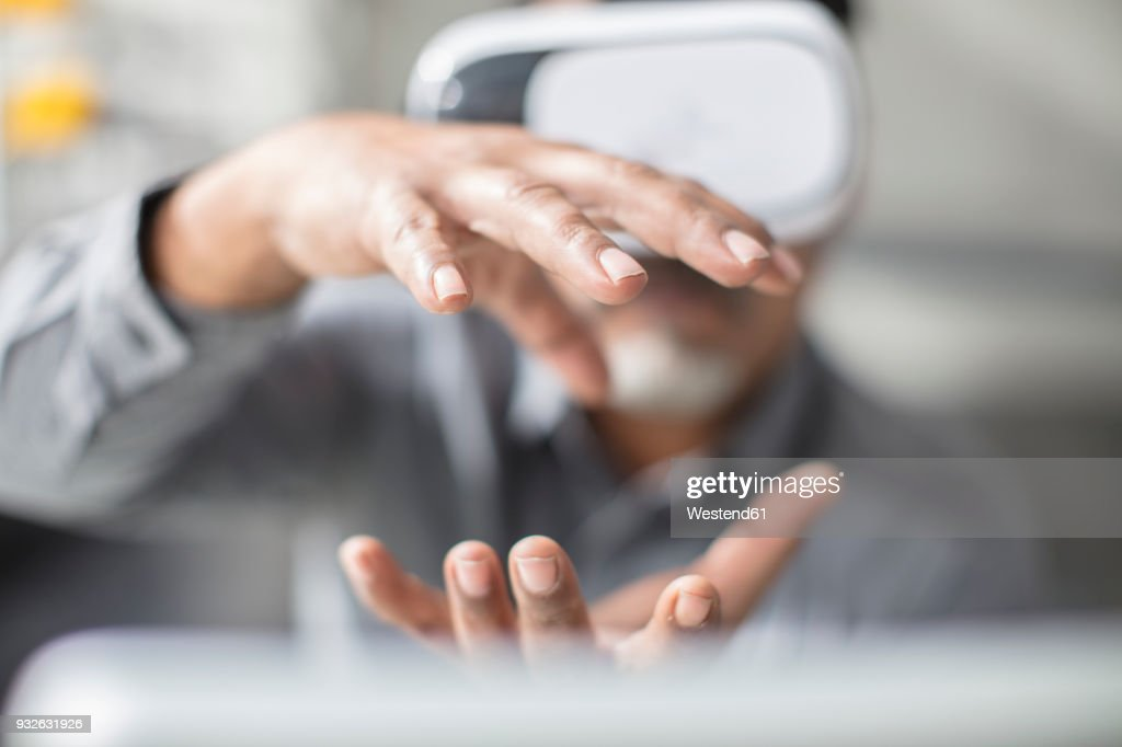 Man shaping with his hands wearing VR glasses in office : Stock-Foto