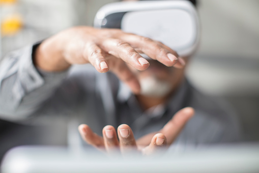 Man shaping with his hands wearing VR glasses in office - gettyimageskorea