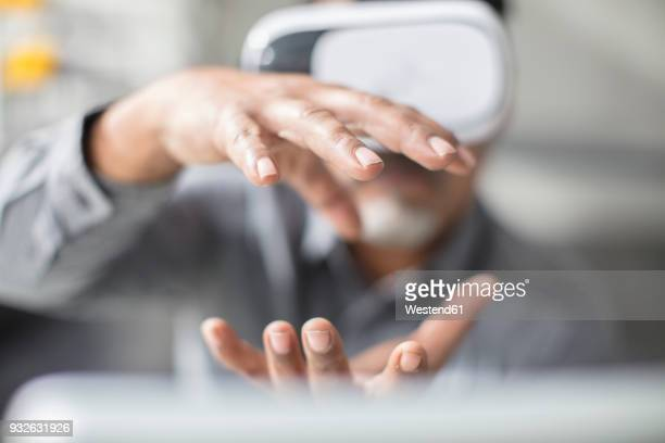 man shaping with his hands wearing vr glasses in office - virtual reality simulator stock photos and pictures