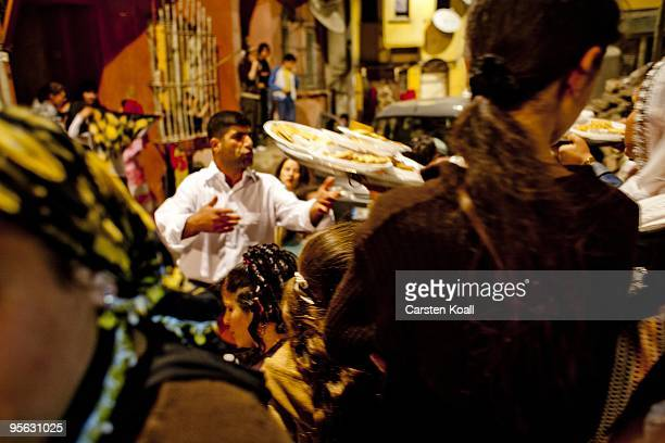 Man shares out sweets for the guests at a wedding party in the district Tarlabasi on May 14, 2006 in Istanbul, Turkey. Tarlabasõ is a neighbourhood...