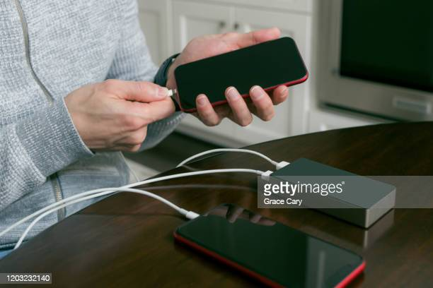 man shares portable battery to charge smart phone - cary stockfoto's en -beelden