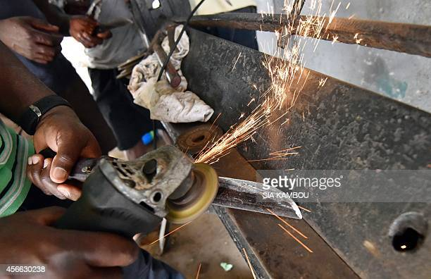 A man sharpen a knife to kill a bull during the first day of the Muslim Eid alAdha on October 4 2014 in Marcory a neighborhood of Abidjan Eid alAdha...