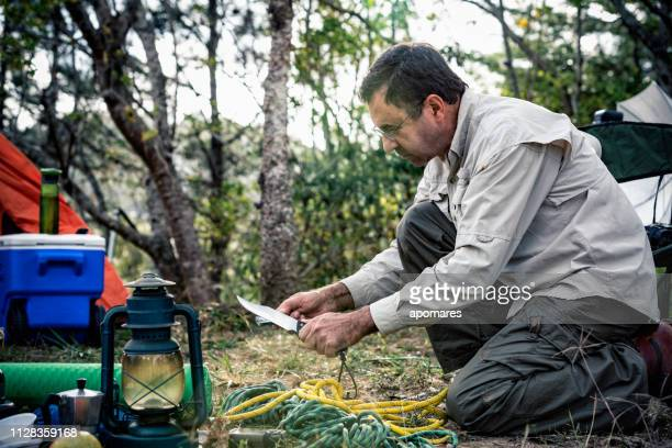 man sharpening knife outdoors in the wilderness - utility knife stock pictures, royalty-free photos & images