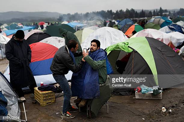 A man shaves a migrant at the Idomeni refugee camp on March 15 2016 in Idomeni Greece The decision by Macedonia to close its border to migrants on...