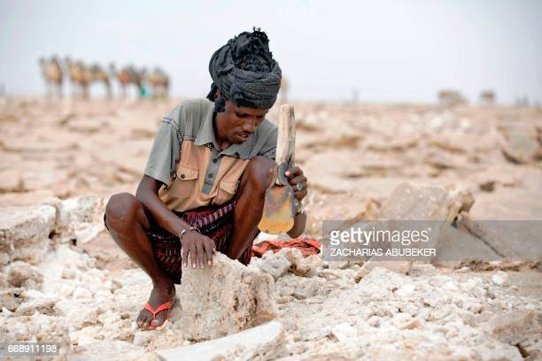 Man shaves blocks of salt from the Danakil Depression on 28 March 2017, in Afar, Ethiopia. Every morning, hundreds of men converge on a dry lakebed...