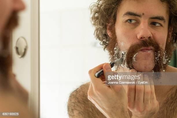 Man Shaving Beard While Looking In Mirror At Home