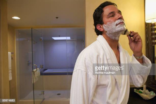Man shaving before bathroom mirror